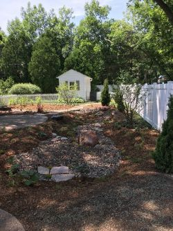 Rain garden, native plants, boulders and decorative stone